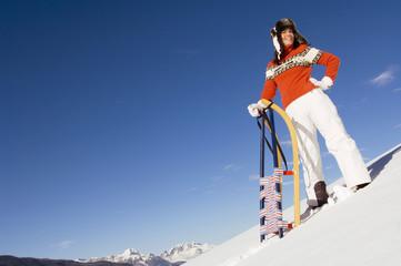 Frau in den Bergen mit Schlitten