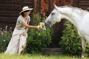 Pferd riecht an Blumenstrauß von Frau