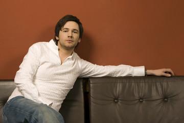Junger Mann sitzt auf Ledercouch