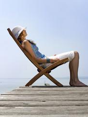 Junge Frau sitzt auf Liegestuhl am Steg, Seitenansicht