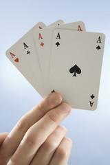 Hand hält vier Asse