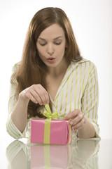 Junge Frau öffnet ein Geschenk