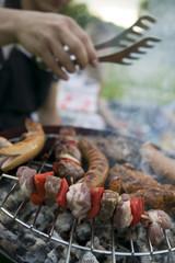 Fleisch und Wurst auf dem Grill, Menschen im Hintergrund