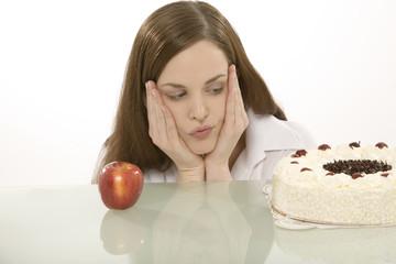 Junge Frau mit Apfel und Kuchen, Thema gesunde Ernährung