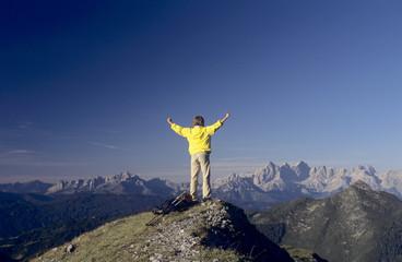 Österreich, Salzburger Land, Mann auf der Spitze des Berges mit den Armen oben