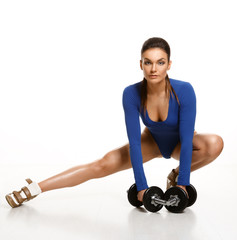 Woman bodybuilder in blue bodysuit, performs an exercise with du