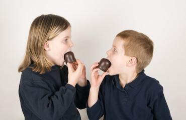 Jungen und Mädchen essen Schokolade Marshmallows