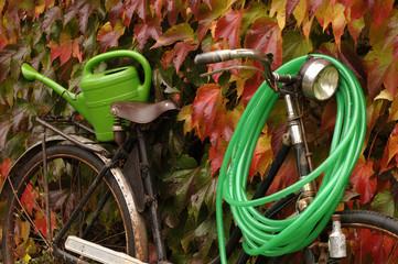 Fahrrad mit Schlauch und Gießkanne im Herbst
