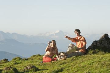 Junges Paar mit Fernglas in den Bergen
