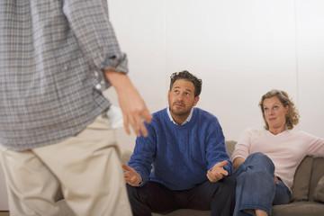 Eltern im Gespräch mit Sohn, Rückansicht