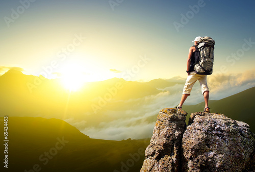 canvas print picture Tourist on rock. Sport and active life concept