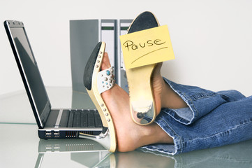Frau bei der Arbeit mit Füssen auf dem Schreibtisch
