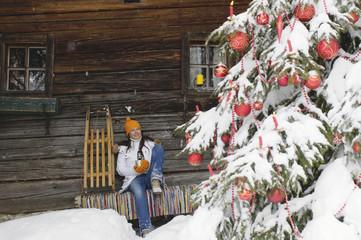 Frau sitzt vor Berghütte, Blick auf Weihnachtsbaum
