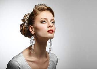 Portrait of a beautiful girl in a white dress and big earrings.
