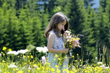 Mädchen mit Blumenstrauß in der Sommerwiese