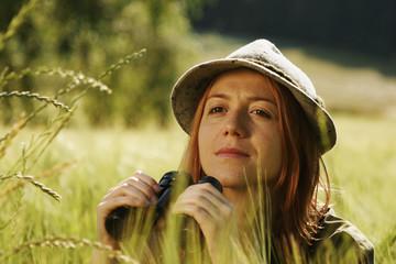 Junge Frau mit Fernglas im Feld