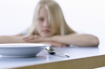 Mädchen blickt auf leeren Teller