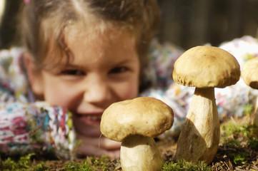 Mädchen sammelt Steinpilze im Wald