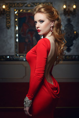 Fashion portrait of young magnificent woman in red dress