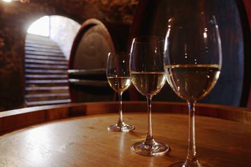 Weißwein in den Gläsern auf Weinfass