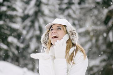 Österreich, Salzburger Land, Altenmarkt, Junge Frau mit Handy in verschneitem Wald