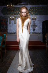 Fashion photo of young magnificent woman in white dress.