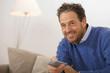 Mann sitzen auf dem Sofa, mit Fernbedienung