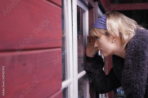 Junge Frau schaut durch Fenter in ein Haus
