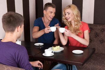 three young people drinking coffee.