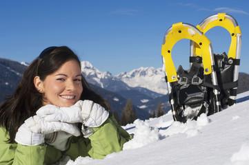 Frau mit Schneeschuhen im Schnee liegen