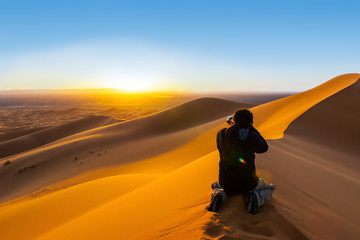 man with dreadlocks taking a photo of sunset from a sand dune