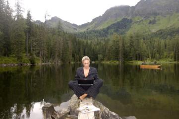 Geschäftsfrau sitzt am See mit Laptop