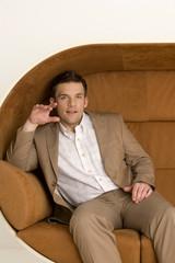 Junger Mann sitzen auf dem Sofa, lächeln, Porträt