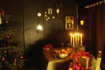 Weihnachtsbaum und brennende Kerzen in Almhütte