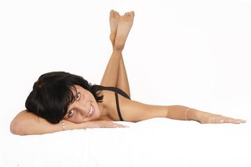 Junge Frau liegt auf dem Bett, lächelnd
