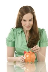 Junge Frau, die Münze in Sparschwein steckt
