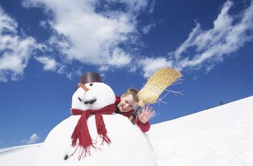 Junge hinter Schneemann mit Besen