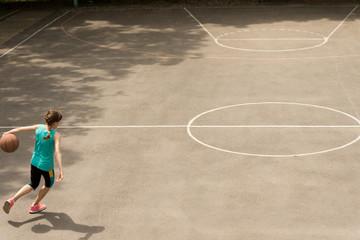 Energetic teenage girl playing basketball