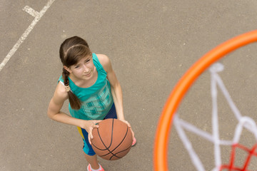 Young girl on a basketball court viewed from above