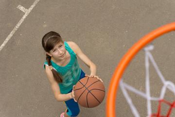 Teenage girl playing a game of basketball