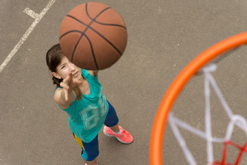 Teenage girl shooting for a goal in basketball