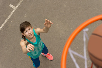 Athletic young girl scoring a goal in basketball