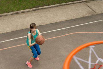 Teenage girl throwing a basketball at the net