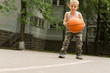 Determined young boy playing basketball