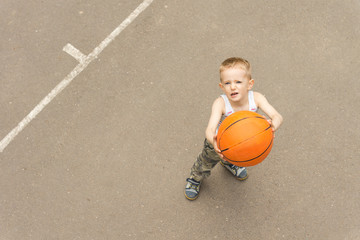 Cute young boy aiming the basketball at the net