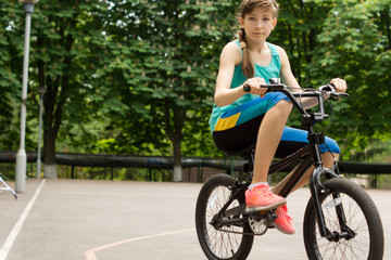 Teenage girl riding a borrowed kids bike