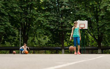 Young boy and girl practising their basketball
