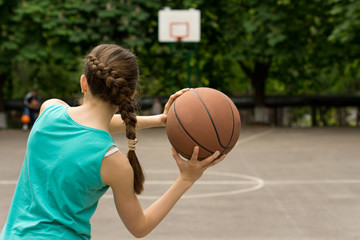 Young slender teenage girl playing basketball