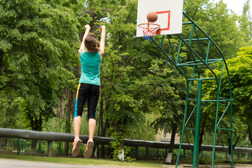 Skilled young basketball player shooting a goal