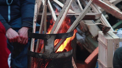 Poor people burn wood trash bin barrel to warm, winter